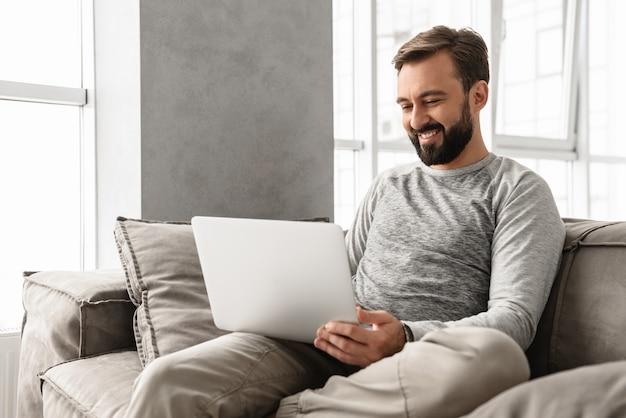 居心地の良い家で仕事をしながらラップトップで入力するカジュアルな服装で満足している30代の成人男性の写真