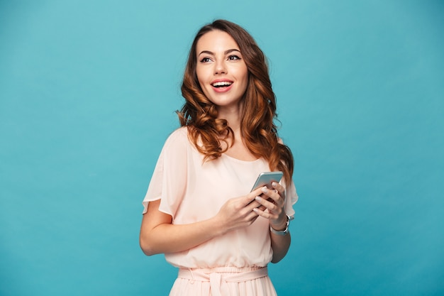 Фотография довольной удивительной женщины, держащей сотовый телефон и смотрящей в сторону на copyspace, изолированной по синей стене