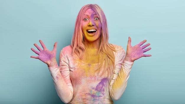 기뻐하는 유럽 여성의 사진은 보라색 얼룩진 손바닥을 보여주고, 손을 뻗고, 행복하게 웃으며, 감정적으로 몸짓을하고, 파란색 벽에 모델을하고, 인도의 holi 연례 축제 행사에서 재미를 느낍니다.