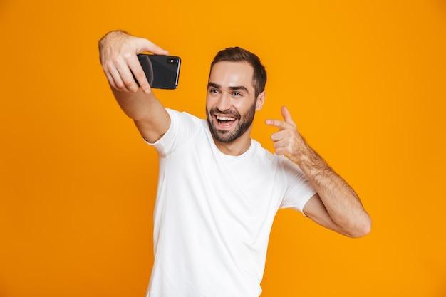 Фотография довольного парня 30-х годов в повседневной одежде, смеющегося и делающего селфи на мобильном телефоне, изолирована