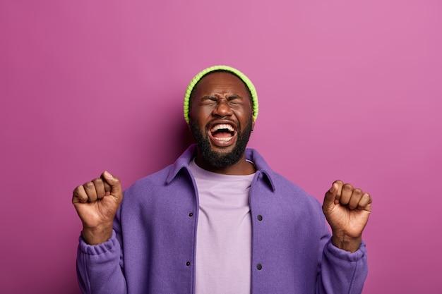 Фотография довольного счастливого хипстера с поднятыми кулаками, веселится на вечеринке, чувствует себя чрезмерно эмоциональным, радостным, щурится от смеха, чувствует себя чемпионом