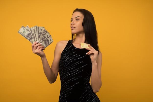 돈과 신용 또는 부채 카드를 들고 노란색 벽 배경 위에 절연 포즈 기쁘게 행복 한 젊은 여자의 사진.