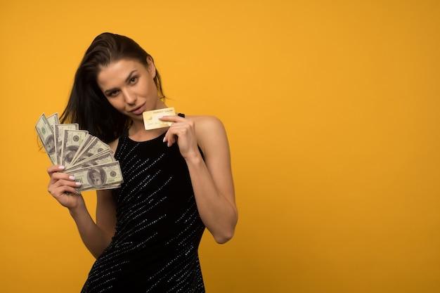 Фотография довольной счастливой молодой женщины, позирующей изолированной на желтом фоне стены, держащей деньги и кредитную или долговую карту.