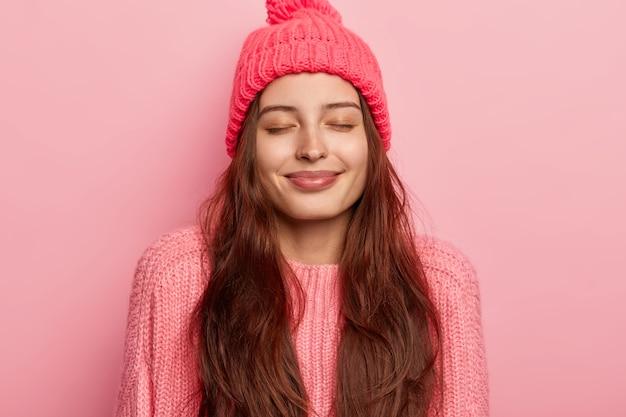 満足している長い髪の満足している白人女性の写真は目を閉じて、優しく微笑んで、健康な肌を持ち、暖かいニット帽とジャンパーを着て、ピンクの背景に対してポーズをとり、何か素敵なものを想像します