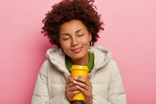 喜んで素敵な巻き毛の女性の写真は、フード付きの暖かいコートを着て、ホットコーヒーを飲み、目を閉じ、ピンクの背景で隔離されます。