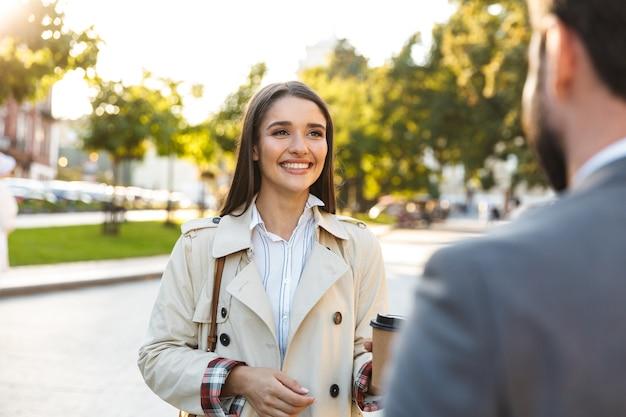 正装でテイクアウトのコーヒーを飲みながら街の通りで話している間お互いを見ている満足しているサラリーマンの男性と女性の写真