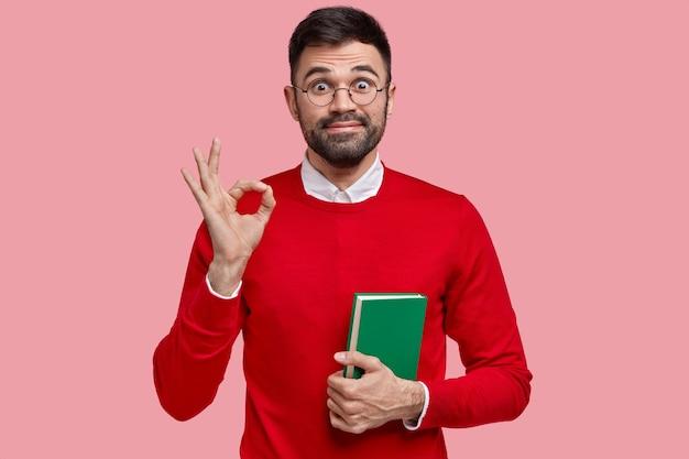 喜んで無精ひげを生やした男の写真は大丈夫なジェスチャーをし、楽しく見え、暗い無精ひげを持って、すべてが大丈夫だと言い、ノートを持っています