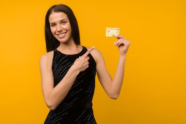 デビットカードまたはクレジットカードを持って喜んでいる若い女性の写真