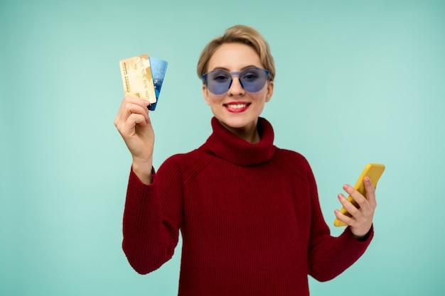 직불 카드를 들고 휴대 전화를 사용 하여 파란색 벽 배경 위에 절연 포즈 기쁘게 젊은 여자의 사진. 카드에 집중
