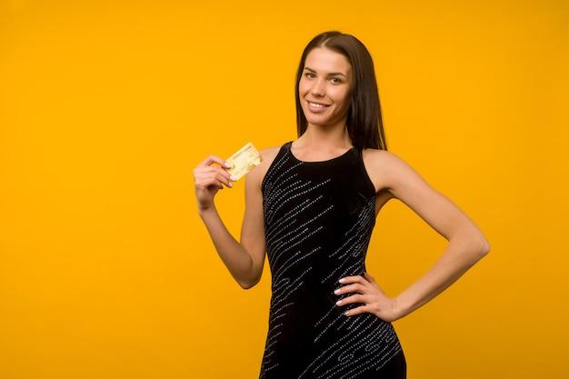 직불 또는 신용 카드를 들고 노란색 벽 배경 위에 절연 포즈 기쁘게 젊은 여자의 사진.