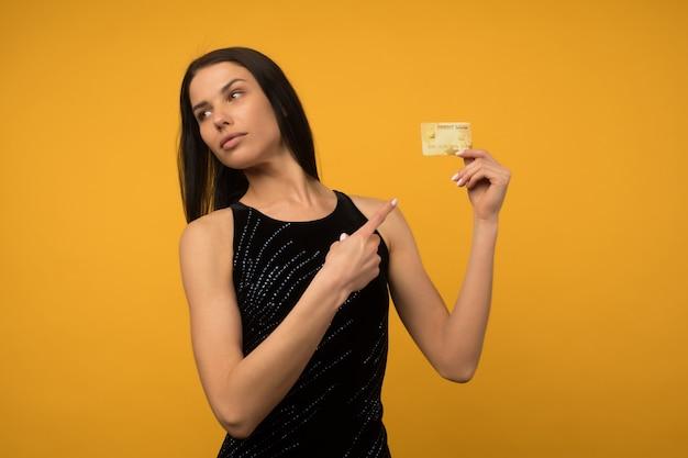 Фотография довольной молодой женщины, позирующей изолированной на желтом фоне стены, держащей дебетовую или кредитную карту.
