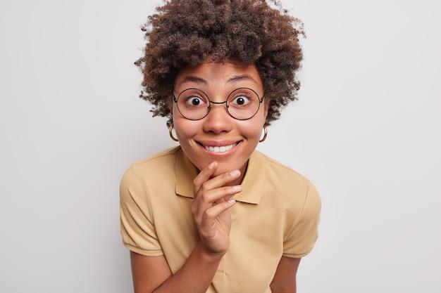 곱슬머리를 한 긍정적인 아프리카계 미국인 소녀의 사진이 턱에 손을 대고 미소를 지으며 기쁜 소식을 주의 깊게 듣고 흰색 배경에 격리된 캐주얼한 베이지색 티셔츠를 입고 둥근 안경을 쓰고 있습니다.