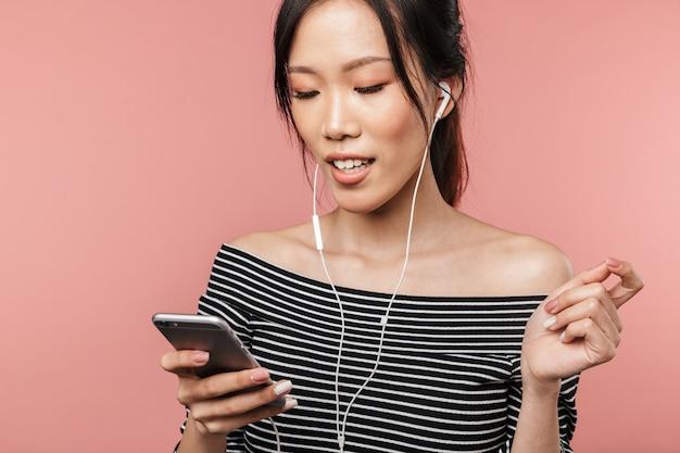스마트폰을 들고 빨간 벽에 격리된 이어폰으로 음악을 듣는 기본적인 옷을 입은 긍정적인 아시아 여성의 사진