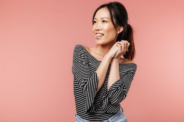 기본 옷을 입은 긍정적인 아시아 여성의 사진은 웃고 붉은 벽 위에 격리된 카피스페이스를 옆으로 바라보고 있습니다.