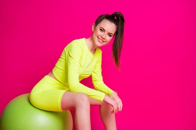 ピンクの明るい輝きの色の背景の上に分離されたポジティブな魅力的なスポーツの女の子の座っているフィットボールの写真