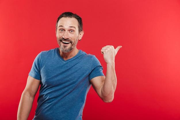 Фотография позитивного бородатого мужчины 30-х годов в повседневной синей футболке рекламного продукта с указательным пальцем назад на copyspace, изолированных на красном фоне