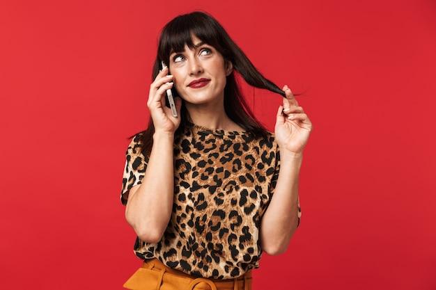 赤い壁に隔離されたスマートフォンで笑顔で話しているスタイリッシュな衣装に身を包んだポジティブなブルネットの女性30代の写真
