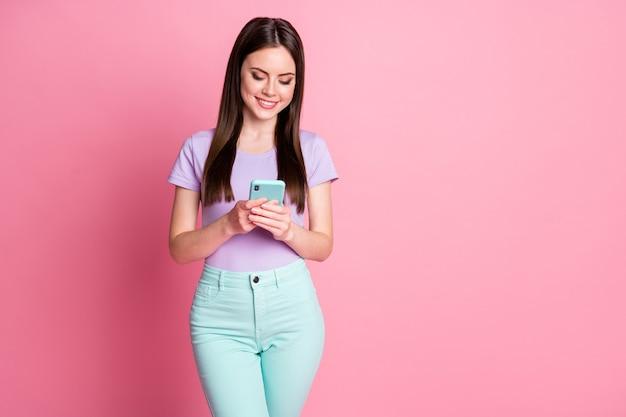 Фотография позитивной жизнерадостной девушки, зависимой от пользователя социальных сетей, читающего новости со смартфона, следуй за комментарием, носи бирюзовые брюки, фиолетовые, изолированные на пастельном цветном фоне
