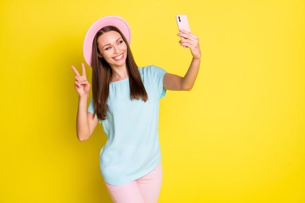 ポジティブな陽気な女の子のブロガーの写真は、旅行を楽しむ旅行を楽しむ自分撮りスマートフォンのビデオ通話を作るvサインを着用する青いピンクのズボンズボン日よけ帽を明るい輝きの色の背景の上に分離
