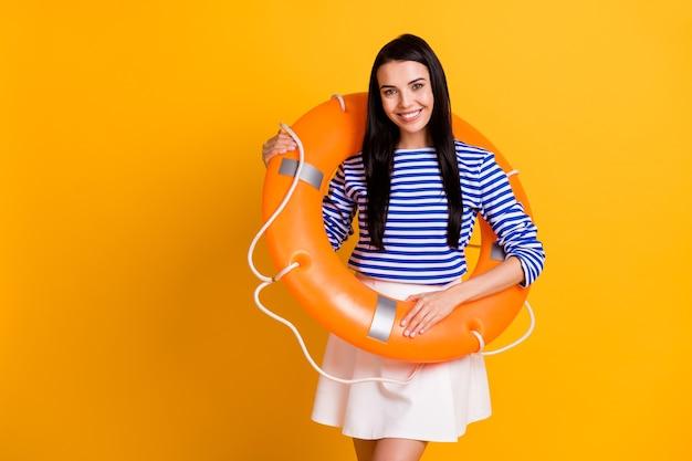 ポジティブで陽気な女の子の写真は、海の水リゾートを楽しんでいますオレンジ色の救命浮環は明るい輝きの色の背景の上に分離された白青の服を着ています