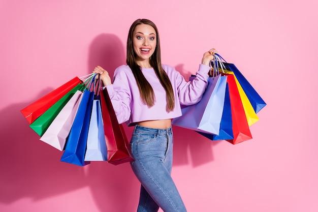 ポジティブで陽気な女の子の写真は、オフセールスで買い物を楽しんでいます-パステルカラーの背景の上に分離されたライラックスタイルのスタイリッシュなトレンディなジャンパーを身に着けている多くのバッグを保持します