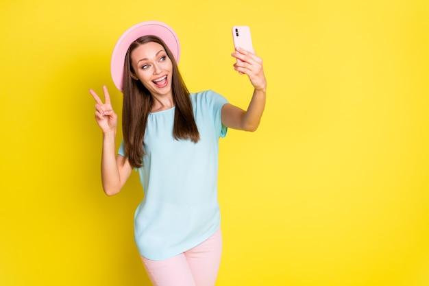 ポジティブで陽気な女の子の写真は旅行旅行を楽しんでいますselfieスマートフォンを取りますvサインを着用ブルーピンクのtシャツパンツズボン日よけ帽を明るい輝きの色の背景に分離