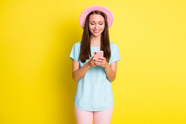 ポジティブな陽気な女の子の写真instagramブロガー使用スマートフォンフォロー購読ニュース着用ピンクのズボンズボンスタイリッシュな日よけ帽を明るい輝きの色の背景に分離