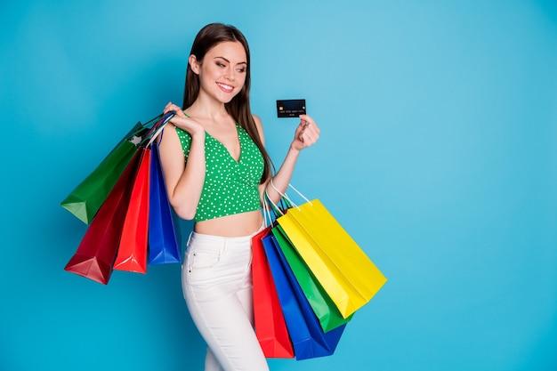 ポジティブな陽気な女の子の外観のクレジットカードの写真は、青い色の背景の上に分離された白いズボンのズボンのタンクトップを着用して有料の買い物袋をお楽しみください