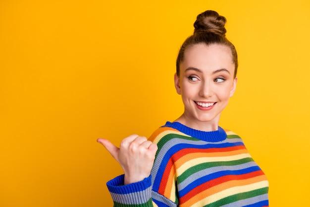 ポジティブな陽気な女の子のプロモーターポイント人差し指のコピースペースの写真は、明るい色の背景の上に分離された広告プロモーションの選択決定アドバイスウェアプルオーバーを示しています