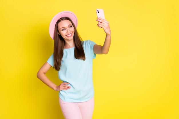 ポジティブで陽気な女の子の旅行者がスマートフォンを使用して、セルフィーを休ませてリラックスした休日のブログを着用してください。明るい輝きの色の背景の上にピンクのズボンを着用してください。