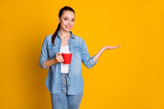 Фотография позитивной уверенной девушки, промоутер, держите руку, вариант показа рекламы, промо-чашка напитка, латте, красивая одежда, изолированная на ярком цветном фоне