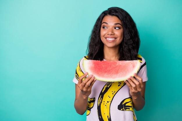 Фотография позитивной темнокожей девушки с ломтиком арбуза выглядит пустым пространством, изолированным на фоне бирюзового цвета
