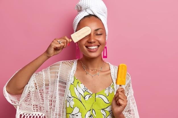 ポジティブなダークスキンの女性の写真は、楽しんで、おいしい冷たいアイスクリームを持って、アイスキャンデーで目を覆い、広い笑顔を持ち、家庭服を着て、ピンクの壁に隔離されています。夏、喜び、食べる