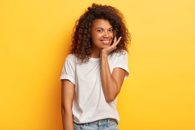 선명한 머리카락을 가진 긍정적 인 어두운 피부 여성의 사진은 부드러운 미소를 가지고 있으며 캐주얼 한 흰색 티셔츠와 청바지를 입은 턱을 만지고 노란색 벽에 서 있습니다.
