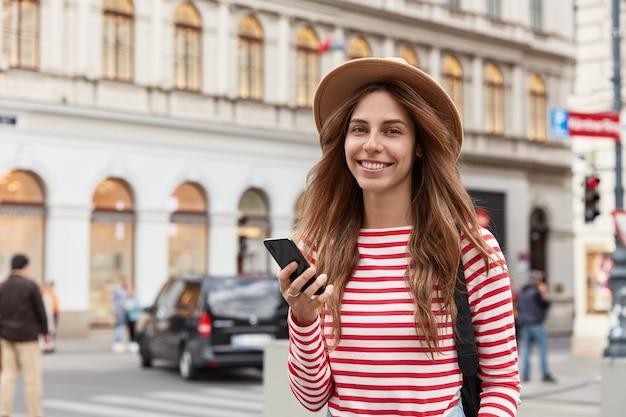 Фотография положительной женщины использует мобильный телефон для навигации по городу, проверяет уведомление