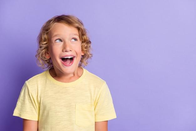 Фотография позитивного забавного мальчика-мальчика, вдохновленного пустым пространством, изолированным на фиолетовом цветном фоне