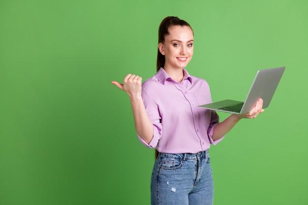 긍정적 인 소녀 ceo 발기인 작업 원격 노트북 포인트 엄지 손가락 copyspace 소셜 네트워크 홍보 광고 보라색 라일락 셔츠 데님 청바지 고립 된 녹색 배경 사진