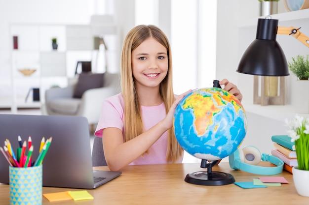 ポジティブな女の子の子供が座っているテーブルデスクの研究リモートユースグローブの写真は、屋内の家で地球大陸を探索したい