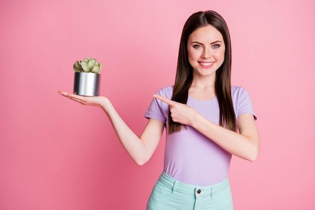 긍정적인 소녀가 꽃 냄비 포인트 검지 손가락을 들고 있는 사진은 생태 안전 개체를 착용하고 분홍색 배경 위에 격리된 청록색 바지 바지를 입습니다.