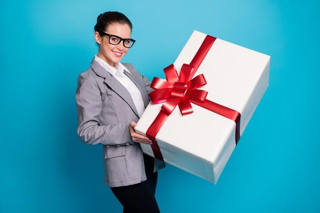 Фотография позитивной девушки-юриста получает большую огромную подарочную коробку в сером пиджаке, изолированном на синем фоне