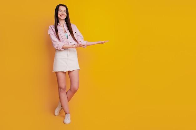 노란색 배경 위에 격리된 긍정적인 소녀 포인트 손가락 빈 공간의 사진