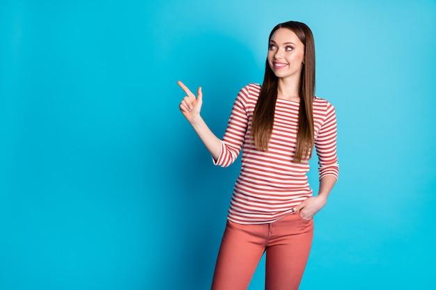 Фотография позитивной девушки-промоутера указывает указательным пальцем на copyspace указывает, что рекламная акция рекомендует выбрать одежду в стиле кэжуал, изолированную на синем фоне.