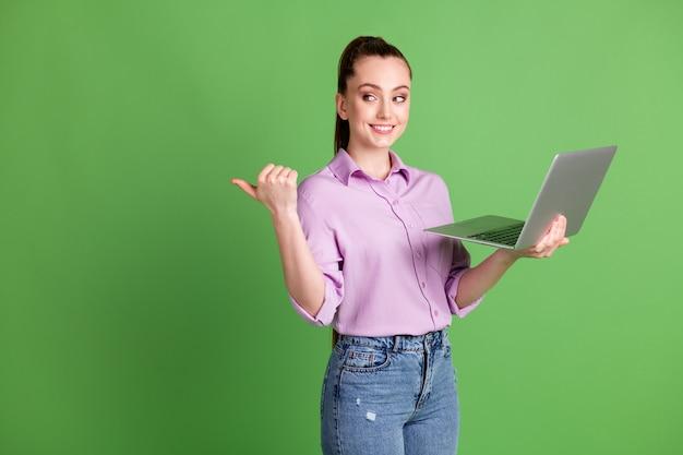 긍정적인 소녀 작업 원격 노트북 포인트 엄지 손가락 카피스페이스의 사진은 소셜 네트워크 프로모션이 녹색 배경 위에 격리된 보라색 라일락 셔츠 데님 스타일의 청바지를 입고 있음을 나타냅니다.