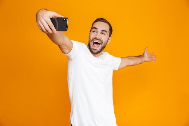Фотография позитивного парня 30-х годов в повседневной одежде, смеющегося и делающего селфи на мобильном телефоне, изолирована