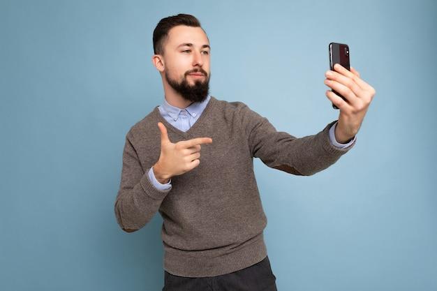 캐주얼한 회색 스웨터를 입고 수염을 기른 긍정적인 잘생긴 젊은 갈색 머리의 면도하지 않은 남자의 사진