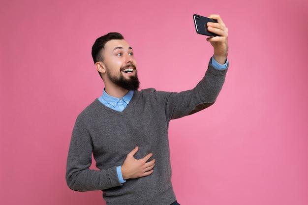 캐주얼한 회색 스웨터를 입고 수염을 기른 긍정적인 잘생긴 젊은 갈색 머리의 면도하지 않은 남자의 사진과