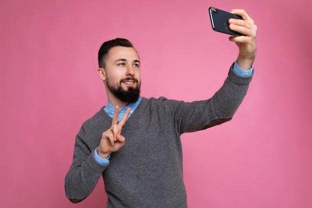 カジュアルな灰色のセーターを着ているひげを持つポジティブなハンサムな若いブルネットの無精ひげを生やした男の写真