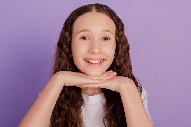 パステルパープルの背景に分離された笑顔を輝いているポジティブな幸せな少女の写真