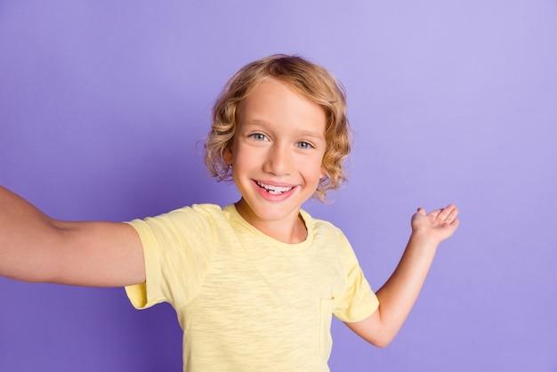ポジティブな子供の男の子の写真は、紫色の背景の上に分離された黄色のtシャツを着て自分撮りを手に空のスペースを保持させます