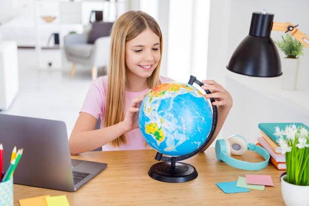 ポジティブな子供の女の子がテーブルデスクに座って離れたホームスクーリングの地理を研究し、家の中で地球大陸を屋内で探索する写真